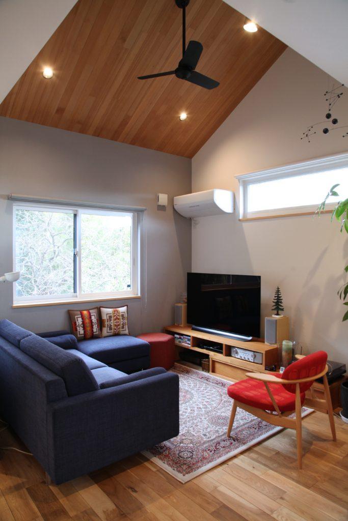 板張りの勾配天井とアクセント壁のリビング