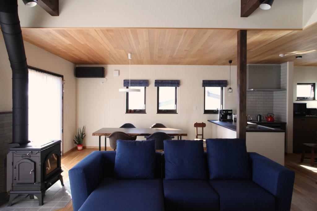 天井板張りと薪ストーブのあるリビング。開放的な対面キッチン。