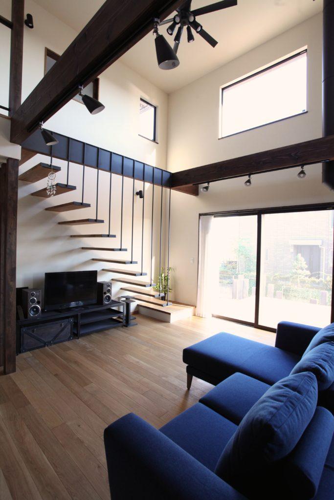 アイアン格子と鉄骨階段。シーリングファンのある吹き抜けリビング。