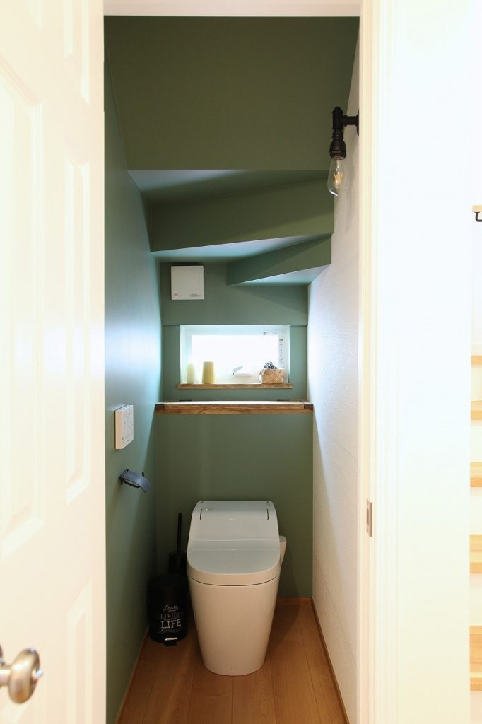 深みのある板の背面収納と落ち着いた色味のアクセントクロス