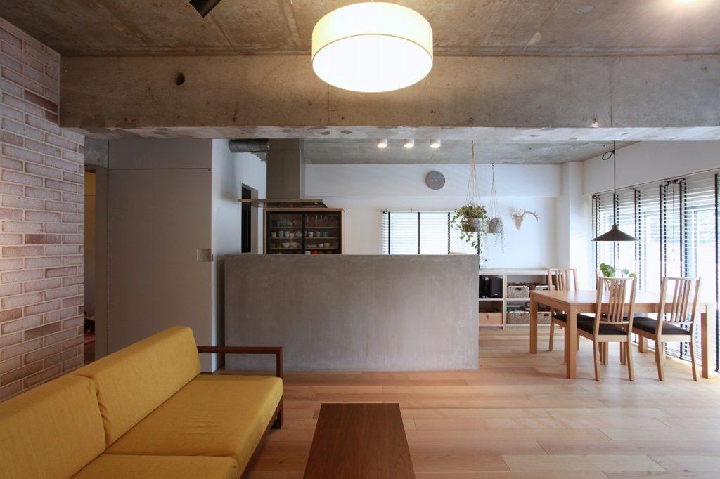 モルタルの腰壁が印象的なオープンキッチンと開放的なリビングダイニング