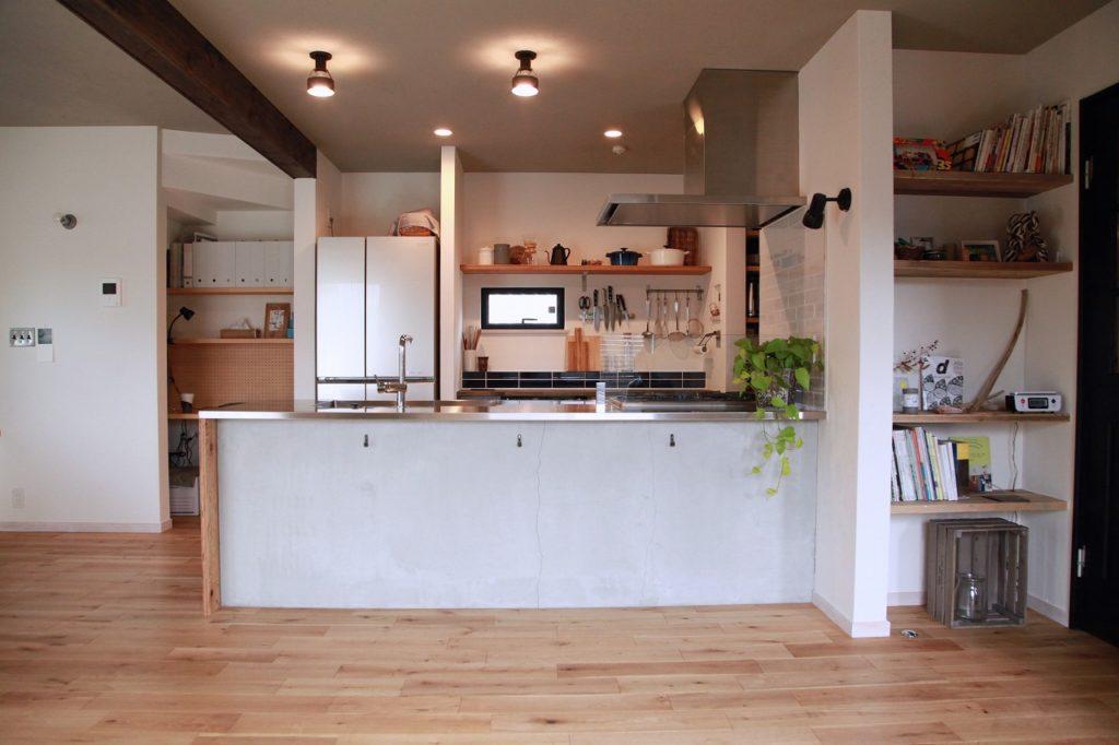 モルタル仕上げの腰壁が印象的な回遊動線キッチンと見せるキッチン背面収納
